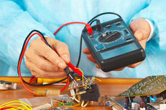 Serviceman checks electronic board with a multimeter. In the service workshop stock images