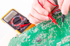 Serviceman checks PCB with a digital multimeter Royalty Free Stock Photos