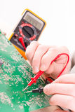 Serviceman checks PCB with a digital multimeter Stock Photography
