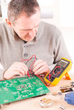 Serviceman checks PCB with a digital multimeter Royalty Free Stock Images