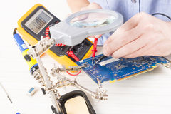 Serviceman checks PCB with a digital multimeter Royalty Free Stock Photo