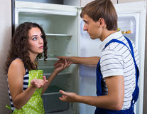 Serviceman and client near refrigerator Royalty Free Stock Image