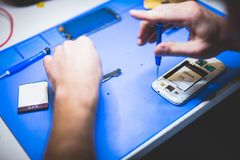 Serviceman fixing broken mobile phone. Damaged devices reparation. Modern technology stock photography