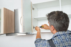 Serviceman Fixing Cabinet With Screwdriver In Kitchen. Rear view of serviceman fixing cabinet with screwdriver in kitchen Royalty Free Stock Images