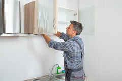 Serviceman Fixing Cabinet With Screwdriver In Kitchen. Rear view of serviceman fixing cabinet with screwdriver in kitchen Royalty Free Stock Photo