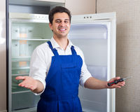 Serviceman fixing technical problems. With fridge at kitchen Royalty Free Stock Image