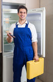 Serviceman fixing technical problems. With fridge at residential lot Stock Images