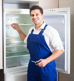 Serviceman fixing technical problems. Positive serviceman fixing technical problems with fridge at residential lot Royalty Free Stock Image
