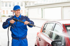 Serviceman With High Pressure Water Jet Washing Car. Confident serviceman with high pressure water jet washing car at service station Stock Images