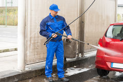Serviceman With High Pressure Water Jet Washing Car. Mature serviceman with high pressure water jet washing red car at service station Royalty Free Stock Photo