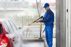 Serviceman With High Pressure Water Jet Washing Car. Mature serviceman with high pressure water jet washing red car at service station Stock Image