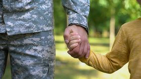 Serviceman holding boys hand, army defending safe future, family togetherness
