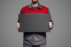 Serviceman holding empty black blank in hands. Gray background. Stock Image