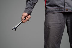 Serviceman holding wrench in hand. Gray background. Stock Image