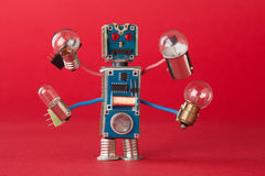 Serviceman illuminator with light bulbs in four hands. Colorful robotic character holds different retro lamps. Funny. Electronic parts. Red background macro Stock Photos