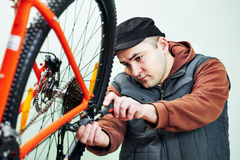 Serviceman installing assembling or adjusting bicycle gear on wh Royalty Free Stock Image