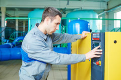 Serviceman operating industrial water purification or filtration equipment Stock Photo