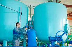 Serviceman operating industrial water purification or filtration equipment. Worker serviceman operating industrial water purification filtration equipment in Stock Photography