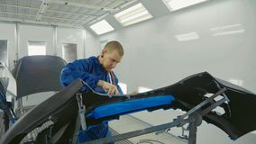 Serviceman preparing a car bodykit for painting in a workshop Royalty Free Stock Image