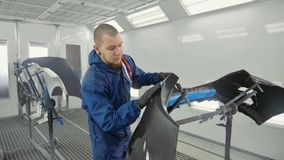Serviceman preparing a car bodykit for painting in a workshop Stock Image