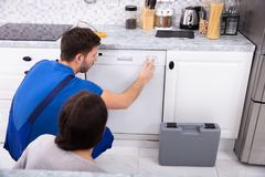 Serviceman Pressing Button Of Dishwasher In Kitchen. Serviceman Crouching On Kitchen Floor Pressing Button Of Dishwasher While Woman Looking At Him stock photos
