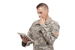 Male soldier looks at his tablet. Serviceman reads off his tablet Stock Photos