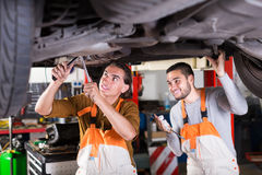 Serviceman repairing car of client Stock Images