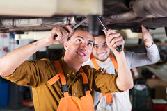 Serviceman repairing car of client Stock Photos