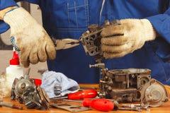 Serviceman repairing old car engine carburetor. Serviceman repairing the old car engine carburetor royalty free stock photos