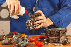 Serviceman repairing parts of automobile engine in workshop Stock Photos