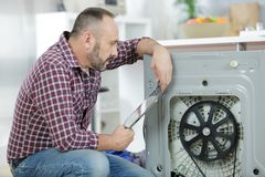 Serviceman repairing washing machine looking at tablet. Serviceman stock image