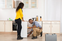 Serviceman Repairing Washing Machine. Young Worker Repairing Washer In Kitchen Room Royalty Free Stock Photos