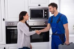 Serviceman Shaking Hands With Woman. Smiling Young Male Serviceman Shaking Hands With Happy Woman stock photography