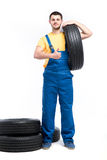Serviceman sitting on tires, white background. Serviceman in blue uniform holds tire in hand, white background, repairman with tyres Royalty Free Stock Images