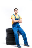 Serviceman sitting on tires, white background. Serviceman in blue uniform sitting on tires, white background, repairman with tyres Stock Photo
