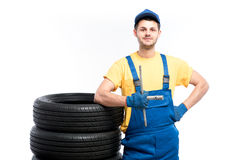 Serviceman sitting on tires, white background. Serviceman in blue uniform sitting on tires, white background, repairman with tyres Royalty Free Stock Image