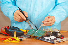 Serviceman solder electronic board of device in service workshop Stock Image