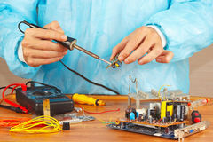 Serviceman solder electronic components of device in service workshop Stock Image