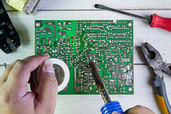 Serviceman soldering circuit board with soldering iron Stock Images