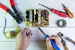 Serviceman soldering circuit board with soldering iron Royalty Free Stock Photo