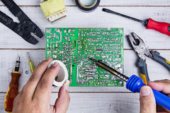 Serviceman soldering circuit board with soldering iron Stock Photo