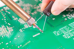Serviceman soldering on PCB Stock Photo