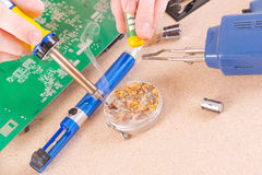 Serviceman soldering on PCB Royalty Free Stock Image