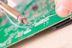 Serviceman soldering on PCB. Serviceman soldering PCB with soldering iron in the service workshop Stock Photo