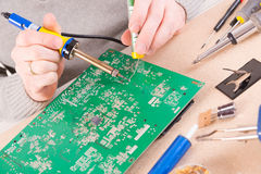 Serviceman soldering on PCB Stock Photography