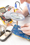 Serviceman soldering on PCB Royalty Free Stock Photos