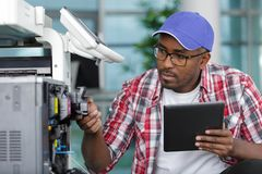 Serviceman with tablet repairing office photocopier. Serviceman royalty free stock image