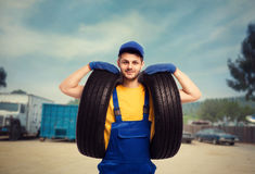 Serviceman in uniform holds tires in hands. Repairman, wheel mounting, tyre service Stock Images