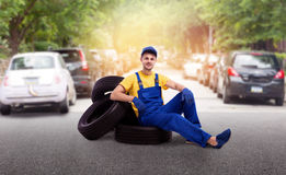 Serviceman in uniform sitting on a pile of tires. Street road on background. Repairman, wheel mounting, tyre service Stock Photos