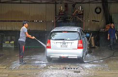 Serviceman is washing a car Royalty Free Stock Image
